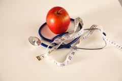 Apple, das auf einer Tabelle mit einem Stethoskop und einem messenden Band liegt Stockfotos