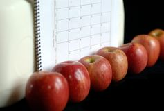 An Apple a Day. Seven apples are lined up against cartons of milk and a calendar.  Only one apple, near the center, is completely in focus.  The seven apples Stock Photo