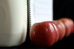 An Apple a Day. Seven apples are lined up against cartons of milk and a calendar.  Only one apple is completely in focus.  The seven apples represent seven days Stock Photos