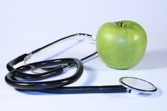 An apple a day. Apple and stethoscope royalty free stock photos