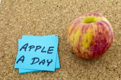 Apple day healthy food habits. Eating daily habits health food red apple a day fruit habit exercise concept sticky postit note reminder Royalty Free Stock Photography