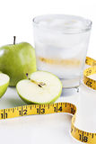 An apple a day helps keep the bulge away. Apple and glass of water with a tape measure royalty free stock photo