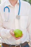 An Apple a day keeps the doctor away. A Doctor with a stethoscope round his neck offering an apple to a member of the public stock illustration
