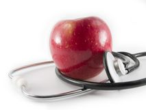 An apple a day keeps the doctor away. A fuji apple with a stethoscope wrapped around it Stock Photos