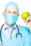 Apple a day keeps the doctor away. A surgeon in a mask and gown wearing a stethoscope holds up a fresh crisp green apple to demonstrate that by eating a healthy Stock Photos
