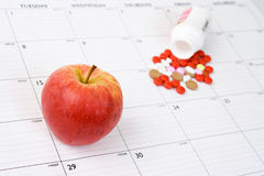 Apple a day keeps the doctor away. Red Apple placed on top of a calendar with bottle of pills in the background.  Focus is on the apple Royalty Free Stock Photos