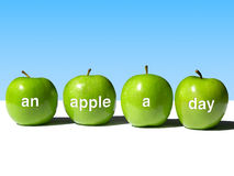 Apple a Day Keeps the Doctor Away. A Row of Four Green Apples Bearing the Words  An Apple a Day  on a White Surface with a Blue Background Stock Image