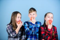 An apple a day keeps the doctor away. Little children biting red apples. Small group of children eating apples together. Cute children enjoying tasty juicy royalty free stock photography