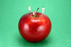 Apple a day keeps the Dr. away. Concept image of miniature doctors standing on an apple, representing the old saying An apple a day keeps the doctor away. The Stock Photo