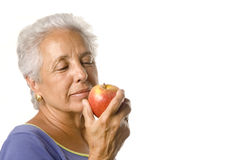 An apple a day kepps ..... Attractive mature woman with an apple Stock Image