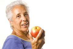 An apple a day kepps ..... Attractive mature woman with an apple Stock Photo