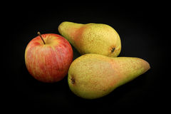 Apple del color rojo y dos peras de color amarillo en una parte posterior del negro Foto de archivo