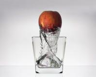 Apple in den glas mit Wasser Lizenzfreie Stockfotos