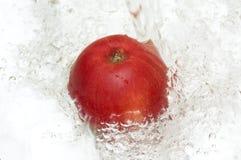 Apple, der im kühlen Wasser spritzt. Lizenzfreie Stockfotografie