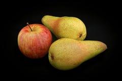 Apple der roten Farbe und zwei Birnen gelbe Farbe auf einer Schwarzrückseite Stockfoto