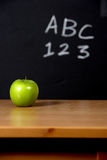 Apple on a desk Royalty Free Stock Photo