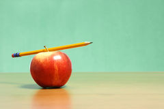 Apple on a desk. An apple on a desk in the classroom royalty free stock photo
