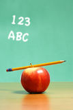 An apple on a desk in a classroom Royalty Free Stock Images