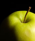 Apple detail. Detail of a green apple in dark back Royalty Free Stock Photography