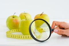 Apple, die band en vergrootglas meten die dieetresultaten voorstellen Stock Foto