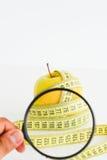 Apple, die band en vergrootglas meten die dieetresultaten voorstellen Stock Afbeeldingen