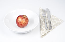 Apple diet. A red apple on a white plate. Fork and knife on serviette. Representing a really strict diet. White background Stock Images
