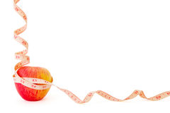 Apple diet frame with copyspace. Big ripe red apple with white measure tape around it metaphore of healthy eating and diet Stock Photo