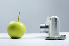 Apple and digital camera. With background Royalty Free Stock Photo