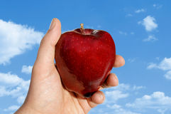 Apple a disposizione contro le nubi Immagine Stock Libera da Diritti