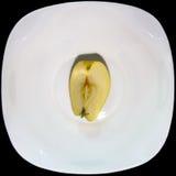 Apple a divisé d'un plat blanc Image stock