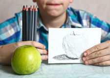 Apple and drawing in kids hands. With different shade coal crayons set close up photo Royalty Free Stock Photography