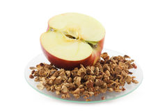 Apple and dried apple pieces. An apple lying on a glass plate with dried apple pieces Stock Image