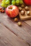 Apple, druva och muttrar Nedgångfrukt på trä Nedgångfrukt och grönsaker på trä royaltyfria foton