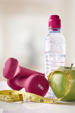 Apple dumbbells and tape on gym white table front view Stock Image