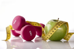 Apple dumbbells and tape measure on white glass table front Royalty Free Stock Photos