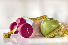 Apple dumbbells and tape measure on white table front gym Stock Photo