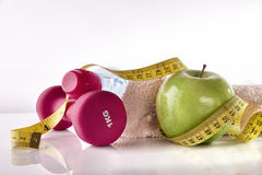Apple dumbbells and tape measure on white table front isolated Royalty Free Stock Photos