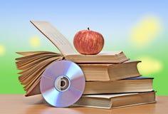 Apple, dvd, y libros imagen de archivo