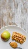 Apple e burro di arachidi in piatto Immagini Stock