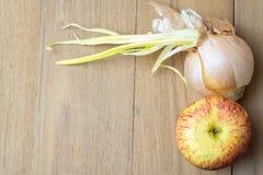 Apple e cipolla sul bordo di legno Fotografie Stock