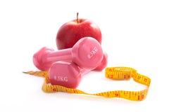 Apple e dumbbells con nastro adesivo di misurazione. Fotografie Stock Libere da Diritti