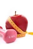 Apple e dumbbells con nastro adesivo di misurazione. Fotografia Stock