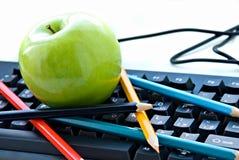 Apple e lápis que encontram-se no teclado foto de stock