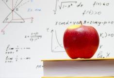 Apple e libro di testo alla scuola Fotografie Stock Libere da Diritti