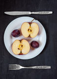 Apple e prugna su un piatto bianco con il coltello e forcella su un fondo scuro Immagine Stock