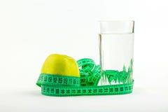 Apple e un metro del bicchiere d'acqua Immagini Stock