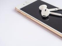Apple EarPods encima del iPhone de Apple Fotos de archivo