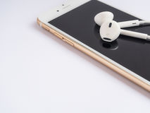 Apple EarPods on top of Apple iPhone stock photos
