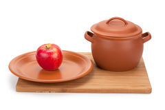 Apple and earthenware crockery on a cutting board Royalty Free Stock Photo