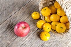 Apple ed arance sul pavimento di legno Fotografia Stock